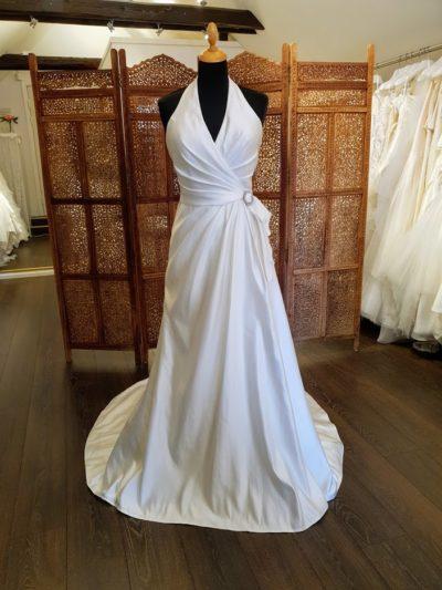 Enkel og smuk satinkjole med et strejf af Marilyn Monroe. Kjolen har draperinger som fremhæver figuren, halterneck, og slæb.