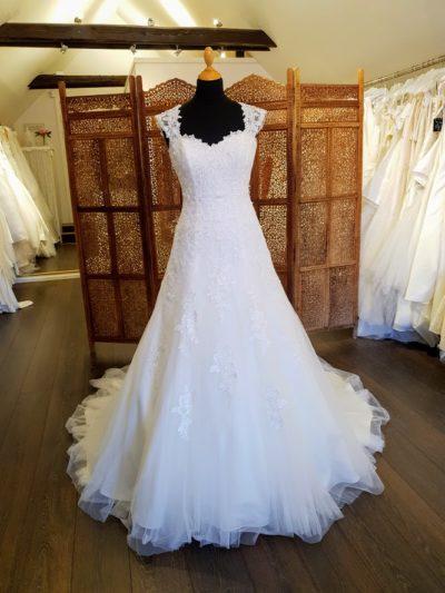 Smuk brudekjole fra Eglantine Creation med masser af blonder. Kjolen har brede blondestropper som evt. kan bruges off-shoulder, lynlåsryg med stofbetrukne knapper og slæb.