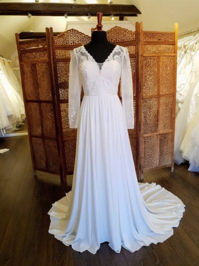 Denne brudekjole fra Real Silk har smukke dekorative blonder, v-udskæring foran og høj ryg bagpå med lynlås og stofbetrukne knapper og lange ærmer. Skørtet i chiffon er let og næsten svævende og danner et smukt slæb.