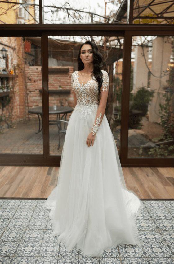 Smuk og dekorativ brudekjole fra Pollardi Fashion Group med masser af blonder, lange ærmer og tylskørt.